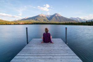 Young woman sitting at the end of a dock